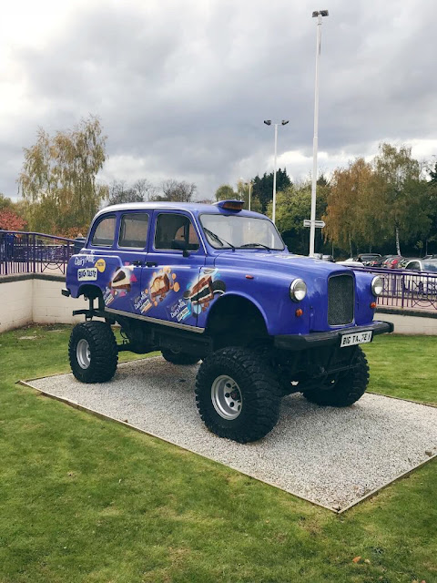 British style taxi on made into a monster truck with big tyres, painted purple and with pictures of chocolates along its side