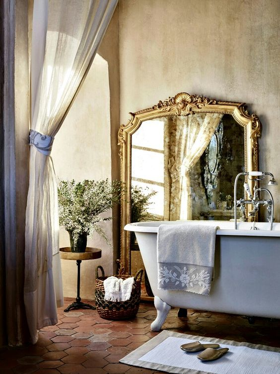 French farmhouse bathroom with plaster walls, clawfoot tub, terracotta floor, and gilded mirror
