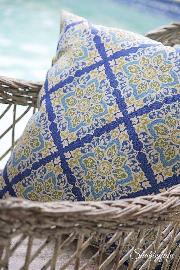 blue pillow on vintage wicker chair