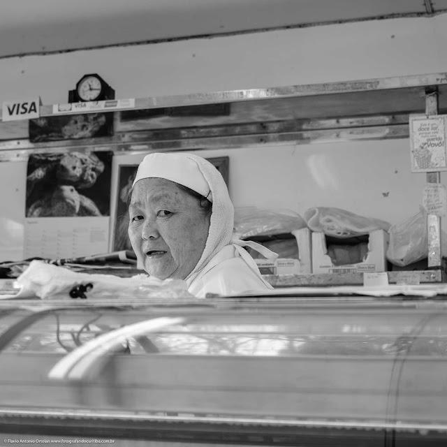 Senhora atendendo na banca de peixes na feira