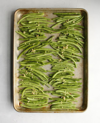 fresh green beans and chopped garlic on a sheet pan ready to be roasted