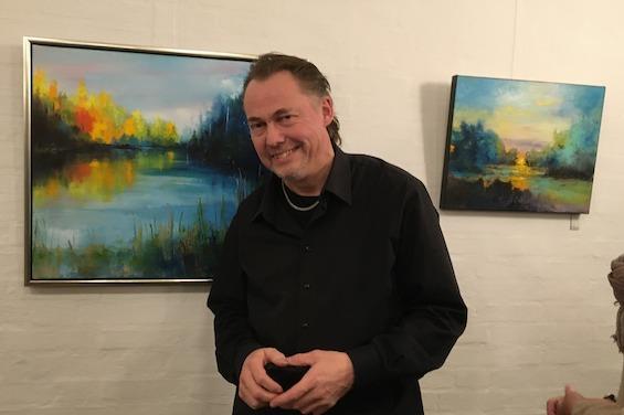 Kaare Norge foran to af hans malerier