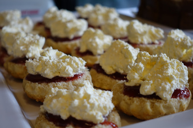 A tray of scones with strawberry jam then fluffy cream on top