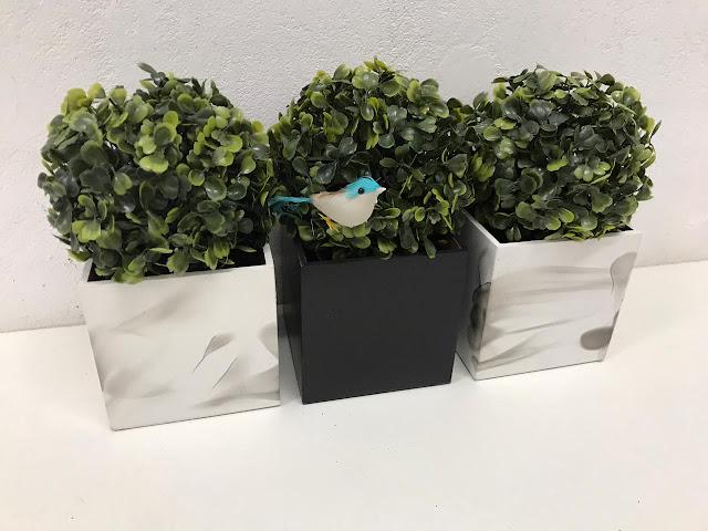 Dois cachepots com pintura que imita mármore e um cachepot preto, todos com plantinhas artificiais do tipo buxinho.