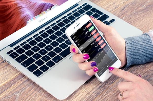 Mãos femininas com um celular na mão cuja tela está aberta em um aplicativo de cotação de ações