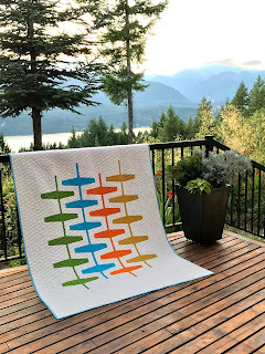 mid-century modern quilt laying over railing in front of mountain scenery