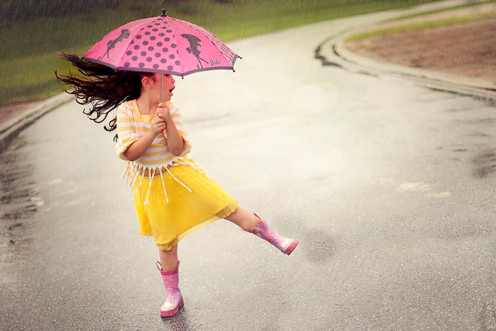 Sweet Little Girl With Umbrella In Rain