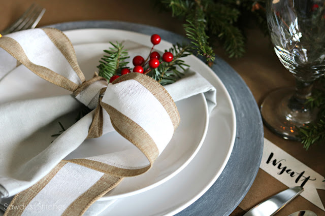 white and silver place setting with a big ribbon bow