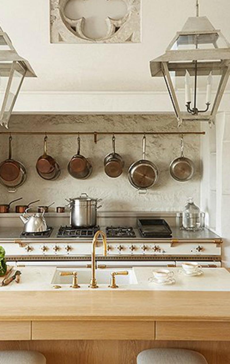 Limestone backsplash in this modern farmhouse kitchen with #Lacanche range, hanging lanterns, and #brasshardware