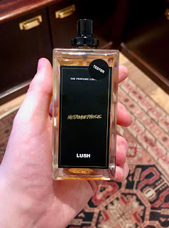A rectangular glass bottle with clear liquid inside with a rectangular black label with metamorphosis in gold font on a bright background