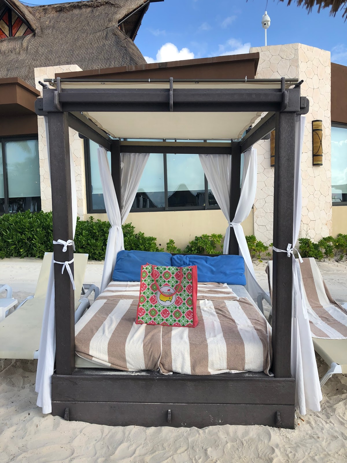a four poster bed is made up on the beach with towels and a beach bag on top of it