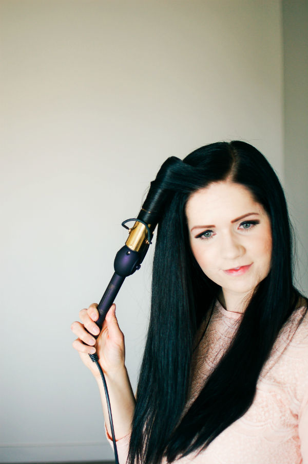 Woman works through how to curl long hair with a curling iron
