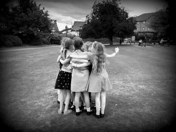 image shows group of young girls hugging in a park