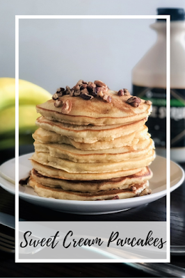 a stack of pancakes topped with walnuts on a white plate with bananas and maple syrup in the background