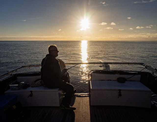 Photo of Phil waiting for the fish to bite as the sun goes down