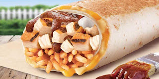 A close up of a cylindrical white tortilla wrap laid on its side cut open to reveal square pieces of brown chicken, white rice and a dark brown bbq sauce on a bright background.