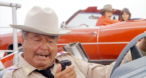 Jackie Gleason talks into a car radio while Burt Reynolds and Sally Field look on