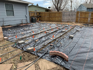Landscaping fabric rolled out over a small area with rows burned into it