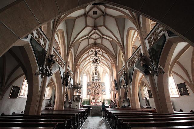 interior de la iglesia de san vicente con imágenes religiosas al fondo