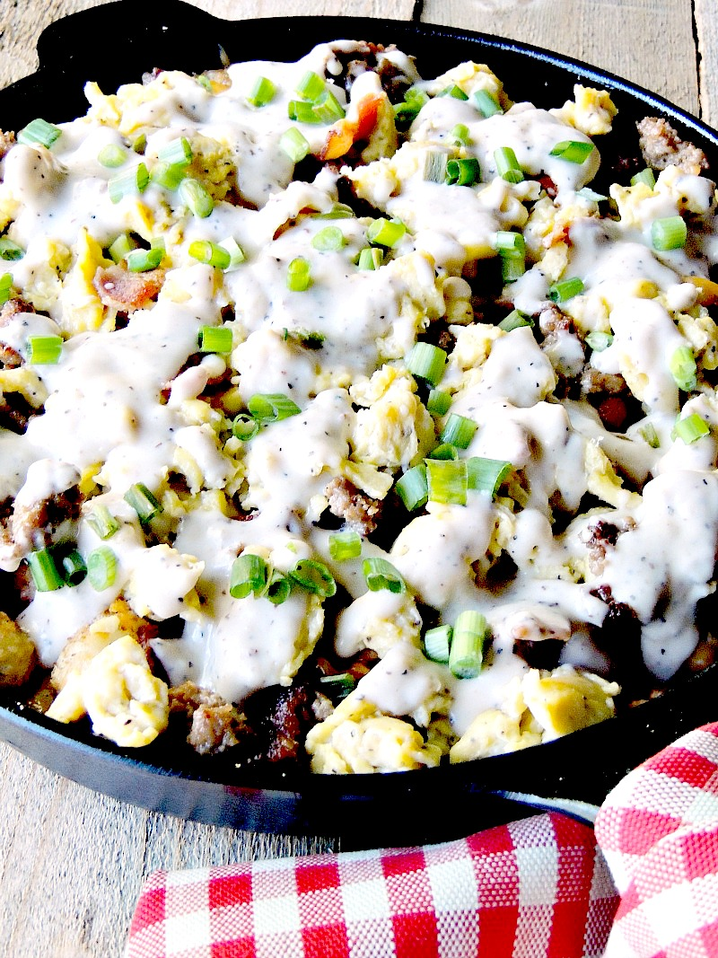 Loaded Breakfast Totchos are crispy tater tots layered with bacon, sausage, cheese, scrambled eggs, and country gravy www.bobbiskozykitchen.com