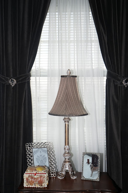 Lamp on side table, with velvet curtains