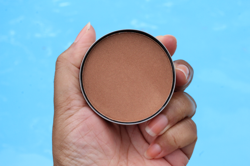 a woman holding bronzer in her hand