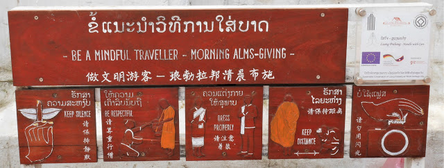 a sign informing tourists of how to behave during the morning alms giving ceremony in Luang Prabang, Laos