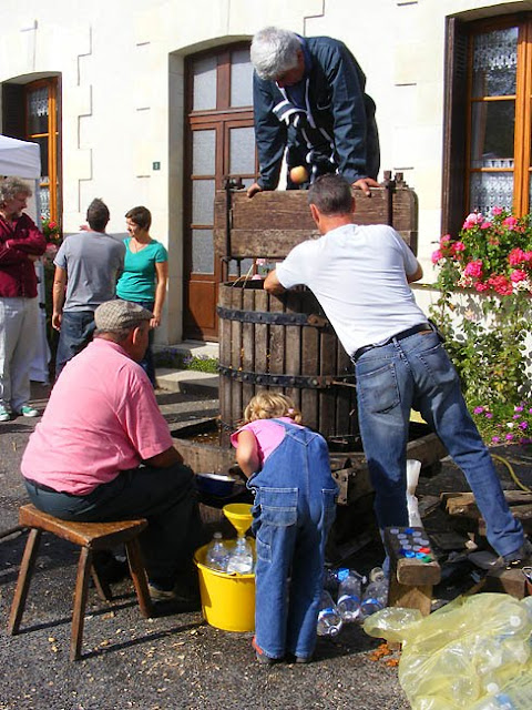 Pressing apples into juice at a village food fair, Indre et Loire, France. Photo by Loire Valley Time Travel.