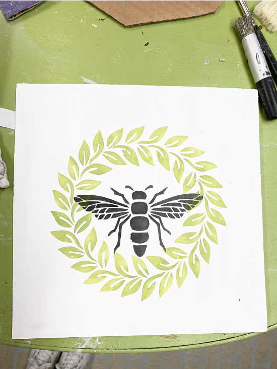 bee and wreath stenciled on a board for the frame