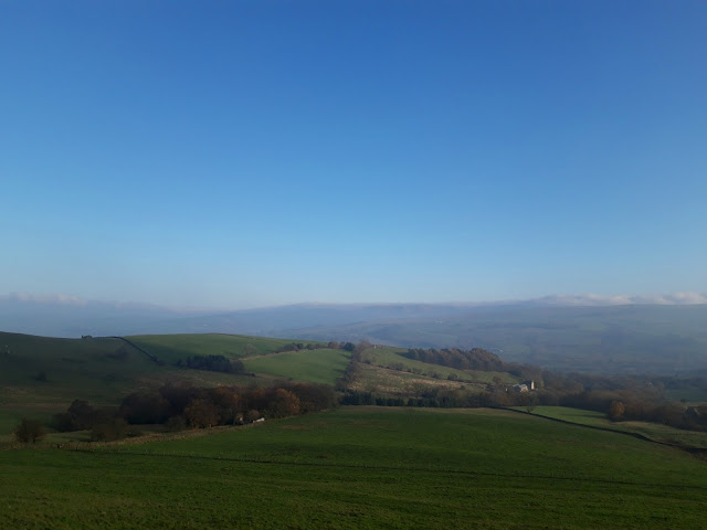 A view across another green Peak District valley.  It's a bright winter morning and the sky is very blue
