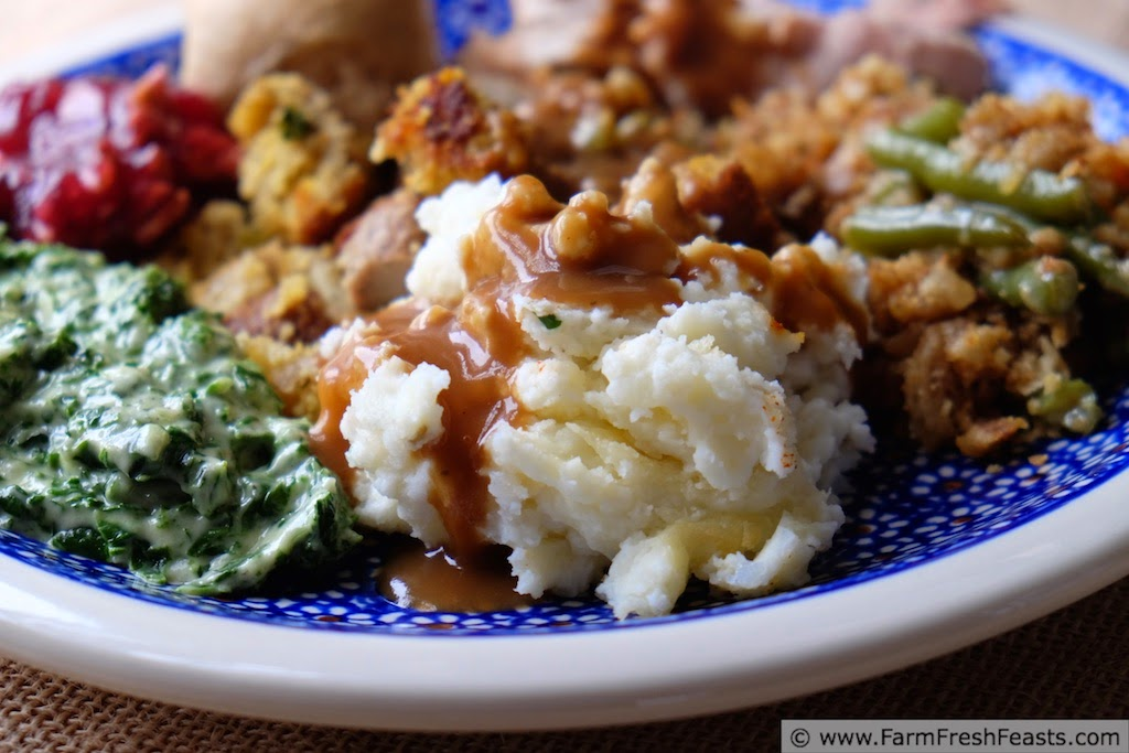 image of a traditional Thanksgiving plate of mashed potatoes, green beans, cranberry sauce, creamed spinach, stuffing, turkey and a roll