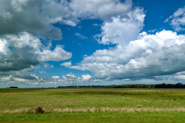 El cielo con nubes sobre un verde campo.