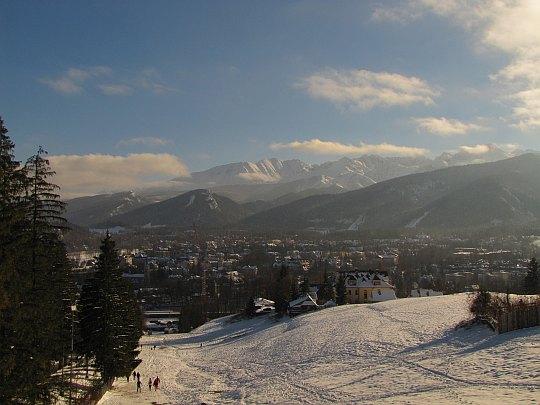 Zza reglowych wzniesień wyrastają szczyty Tatr.
