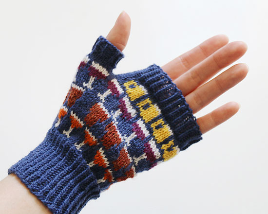 Palm side of hand wearing knit colorwork Drinkers Mitt in blue with details in white, yellow, purple, brown and orange on a white background.