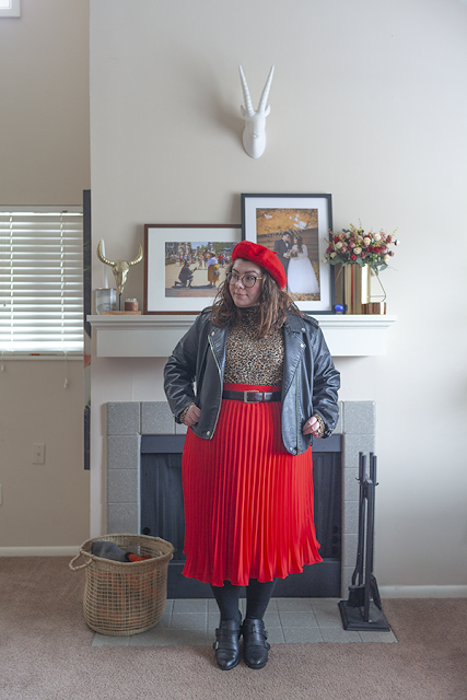 An outfit consisting of red beret, black moto jacket, animal print top tucked into a red pleated midi skirt and black ankle boots.