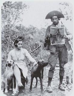 Legenda: Maria Bonita e Lampião em momento de sossego na caatinga, em foto de 1936. Descrição: A fotografia em preto e branco mostra um casal em meio ao cerrado. À direita e em pé, um homem de chapéu com a aba virada para cima, três moedas presas na testeira, casaco, calça com perneiras e alpercatas de couro; ele lê o jornal entre as mãos. À esquerda, uma mulher sentada com a perna direita cruzada sobre a esquerda, ela está com as mãos sobre o lombo de dois cães, um de cada lado. Ela usa duas presilhas sobre o cabelo curto, vestido simples e sandálias.  Ao fundo, a mata do cerrado.