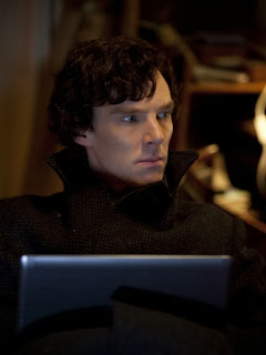 Benedict Cumberbatch as Sherlock Holmes with his laptop in 221 B Baker Street in BBC Sherlock Season 1 Episode 3 The Great Game