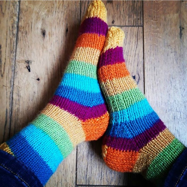 A photo of a pair of feet wearing hand knitted socks taken from above with the sides of the feet showing.  The sock yarn is stripes of yellow, maroon, dark blue, light blue and green.  The background is a wooden floor