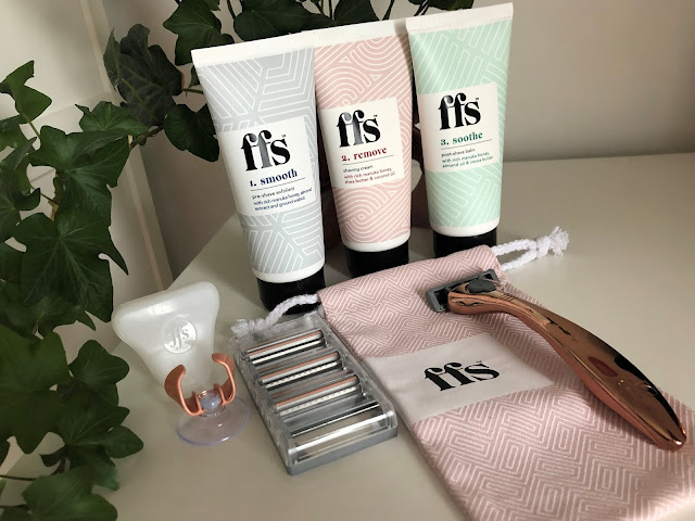 3 tubes behind rose gold razor, small canvas bag, and razor blades with ivy plant in background