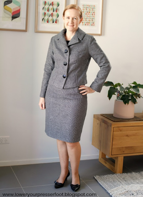 lady posing in a handmade grey skirt suit