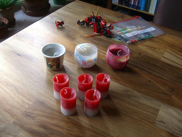 Verschillende zelfgemaakte kaarsen waaronder vijf rood-witte rechte kaarsen die wel een beetje aan een leger doen denken, zie het verhaal.