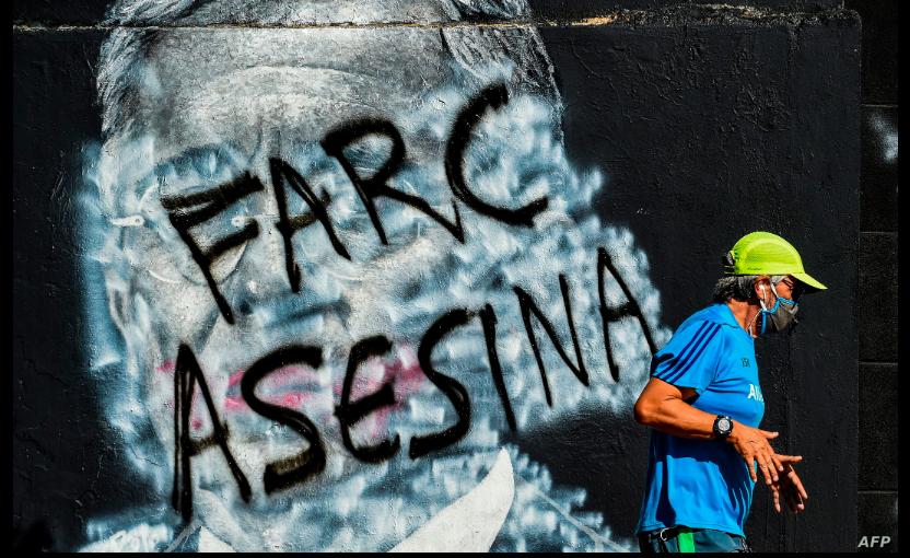 Un hombre pasa corriendo junto a un mural contra el expresidente colombiano (2002-2010) Álvaro Uribe, que fue pintado y ahora muestra un graffiti contra las FARC, una vez grupo guerrillero y ahora el partido político / AFP