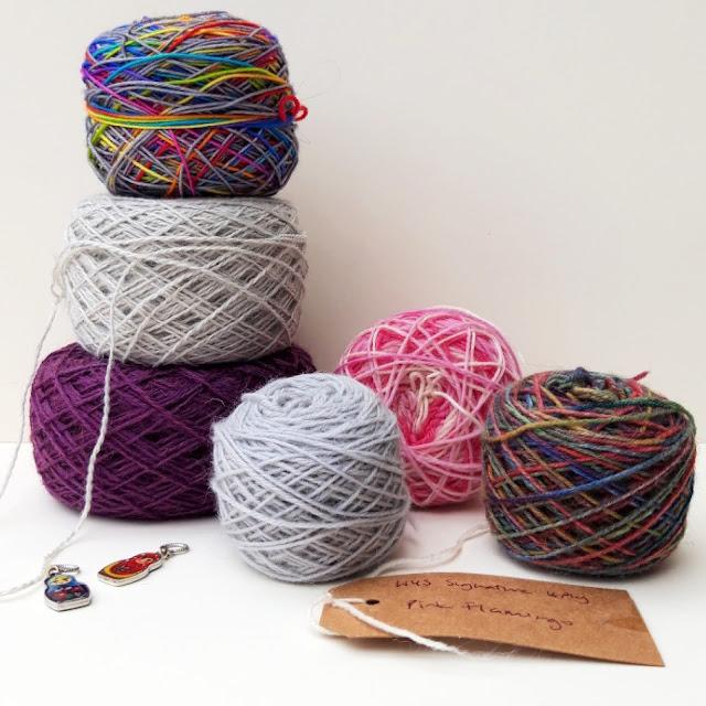 Yarn cakes of various colours stacked on top of each other against a white background