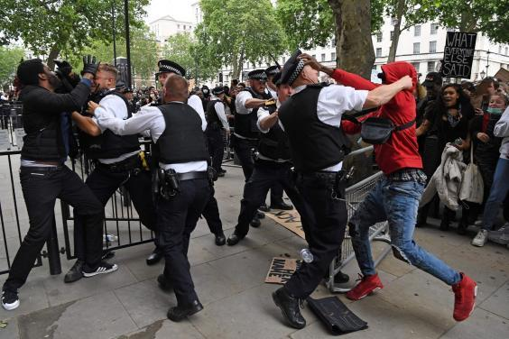 Protesters scuffle with police officers near the entrance to Downing Street