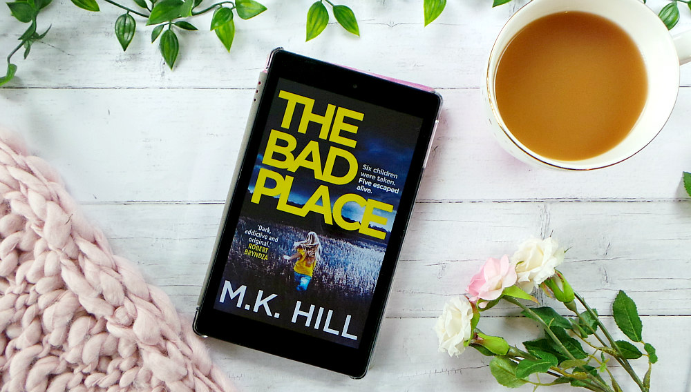 Kindle fire screen showing the cover for the bad place. The cover has a girl with long blond hair wearing a yellow tshirt and jeans running through a field. The background of the image features some leaves, roses, cup of tea and a pink chunky knit blanket