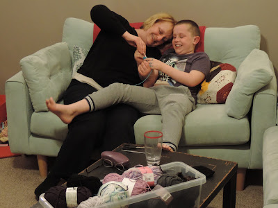 boy and mum giggling on grey sofa