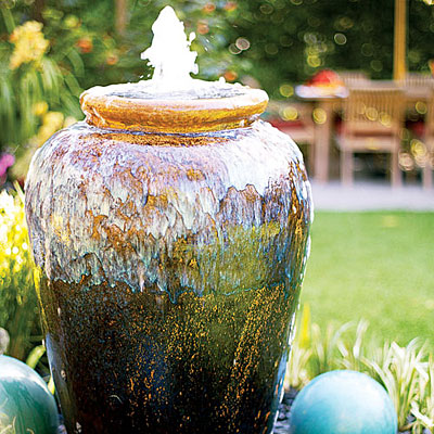 Two men and a little farm fountain in a planter pot vase for Pot water fountain designs
