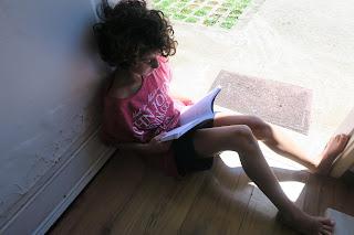 Meu filho lendo na porta de casa aproveitando o sol da manhã