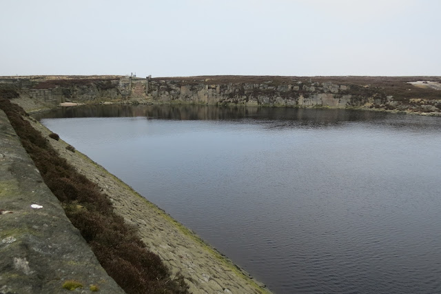 The northern end of Warland Reservoir, edged by sheer rock faces.