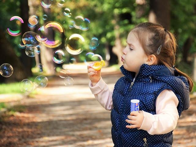 Menina assoprando bolhas de sabão!